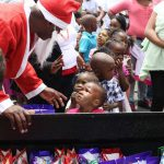 Santa dishes out gifts to a long row of kids