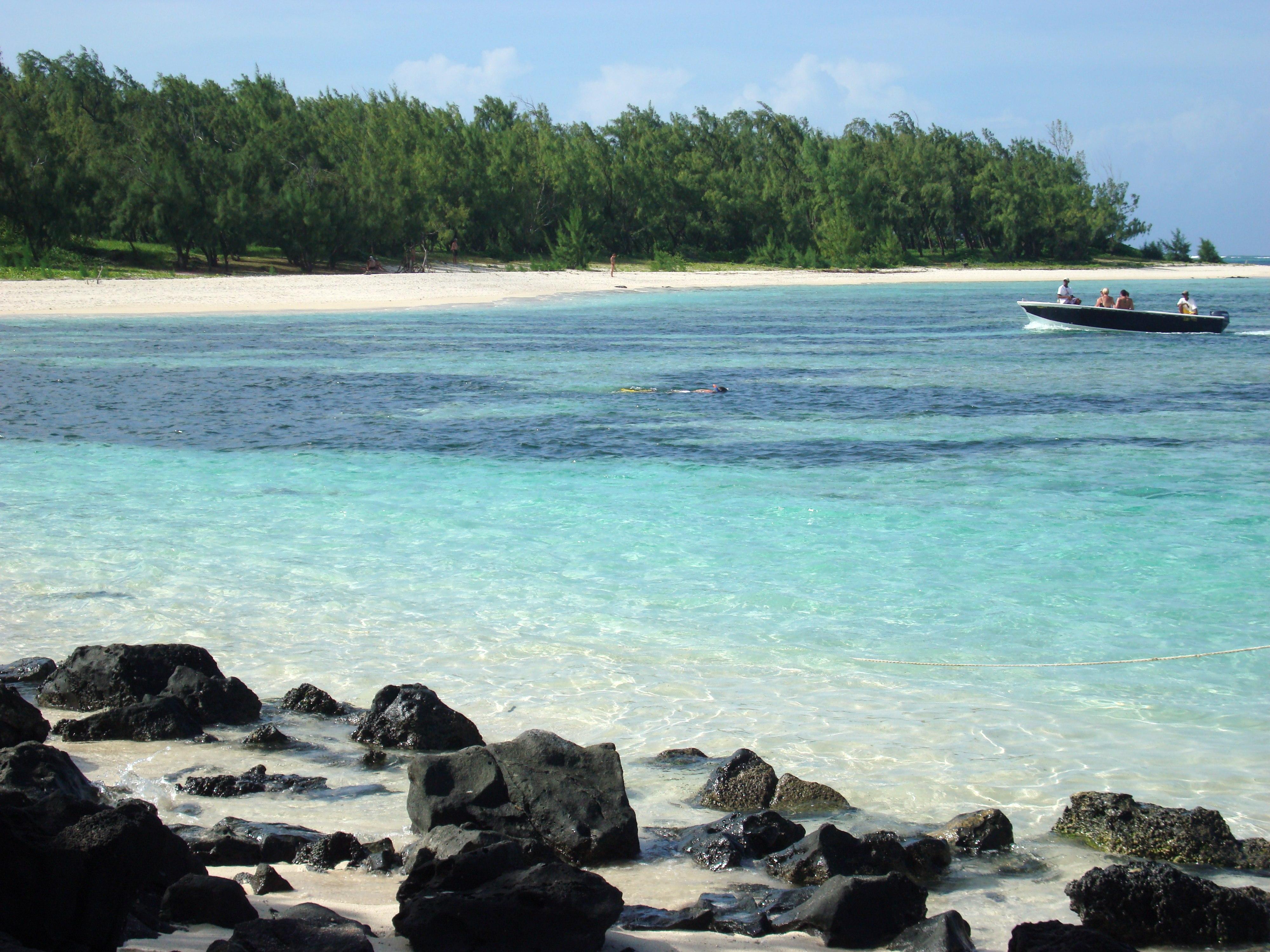 Ein Boot im türkisblauen Waser vor einer Küste mit weißem Sand und grünen Bäumen