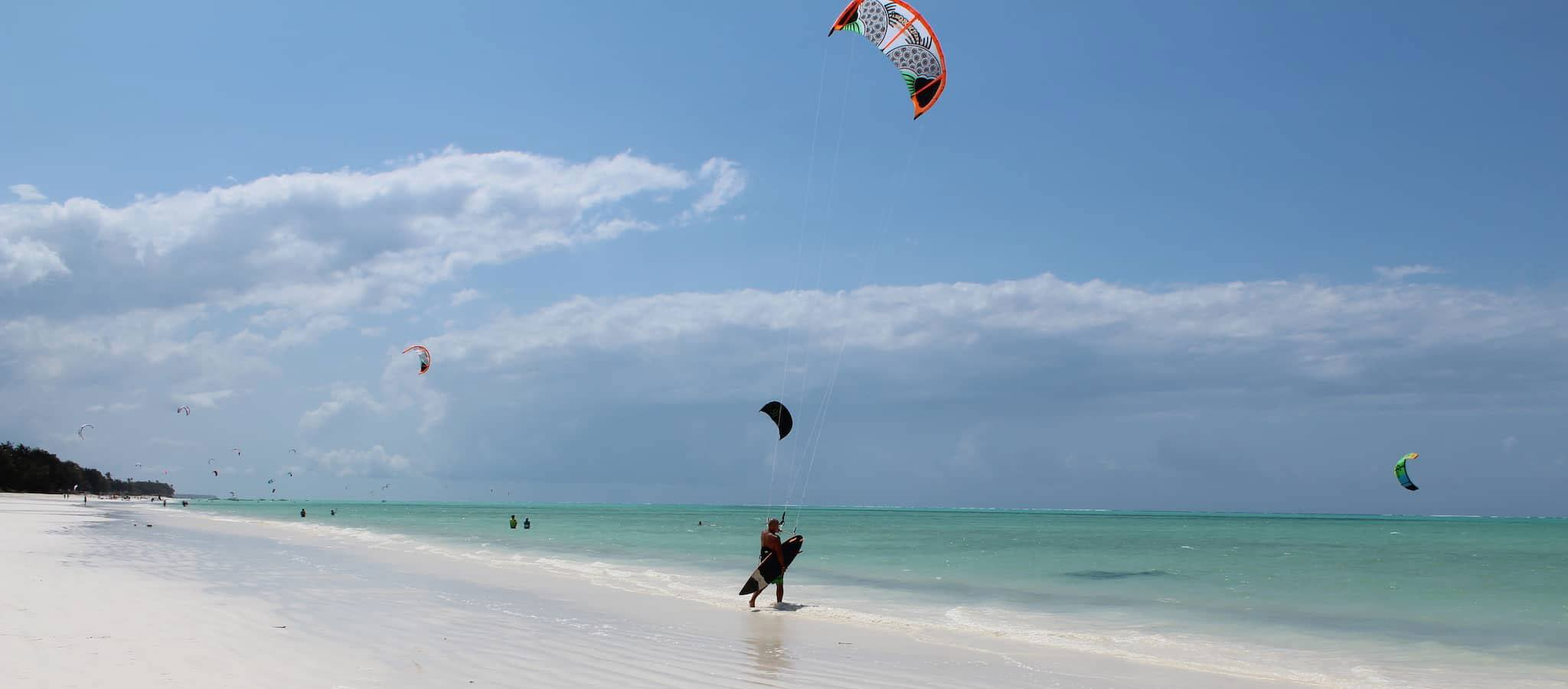 Ein Kitesurfer auf dem Ozean vorm weißen Sandstrand von Sansibar