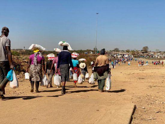 Südafrikaner tragen Säcke Maismehl nach Hause