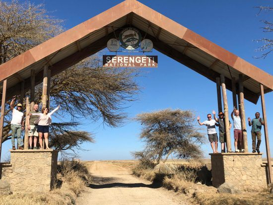 Rhino-Africa-Mitarbeiter posieren am Eingang vom Serengeti Nationalpark